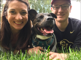 Close-up picture of Katie, her husband, and dog lying in grass