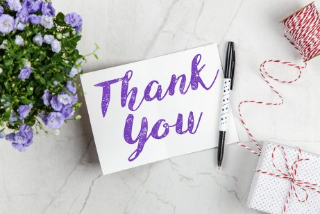 Just-finished thank you note with a pen, surrounded by flowers and small gift